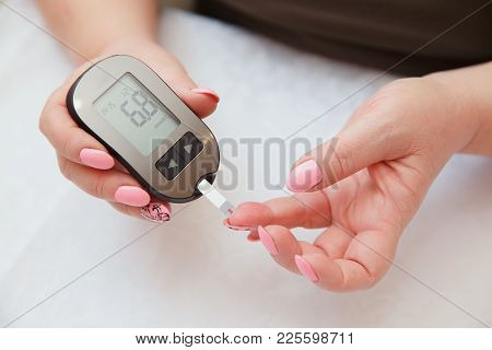 Glucometer. Woman Checks Blood Sugar Level For Diabetes, Insulin Levels