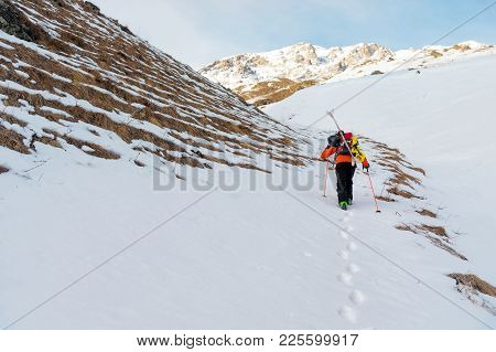 The Ski Freerider Climbs The Slope Into Deep Snow Powder With The Equipment On The Back Fixed On The