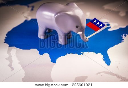 Toy Elephant Holding A Republican Party Flag Over A Usa Map.