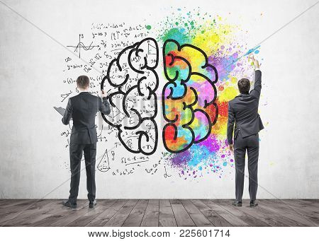 Rear View Of Two Businessmen Drawing A Colorful Large Brain Sketch On A Concrete Wall. Concept Of Cr