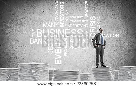 Confident Businessman In Suit Standing On Pile Of Documents Against Business Related Terms On Backgr