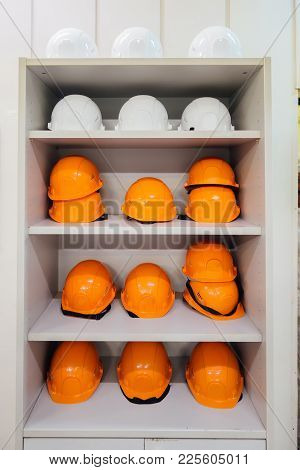 White Cabinet With Industrial Safety Helmets For Builders.