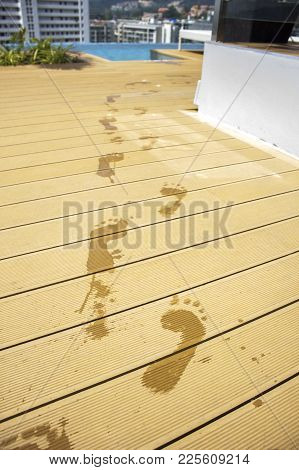 Summer Background. Impressions Of Wet Feet On A Wooden Board. Traces Of Man