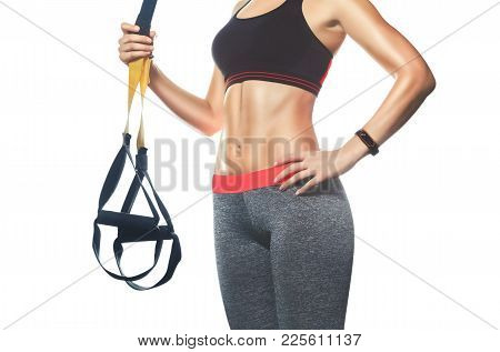 A Slender Girl Holds A Strap In Her Hand For The Suspension Training In The Gym. Sports Concept And