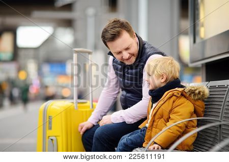 Cute Little Boy And His Father Waiting Express Train On Railway Station Platform Or Waiting Their Fl