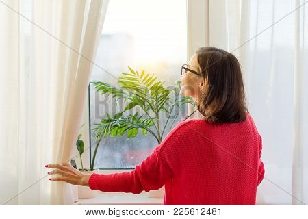 Woman Looks Out The Window, Opens The Curtains. View From The Back.