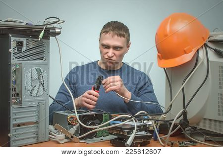 Crazy Computer Network Technician Man Is Crimping A Network Cable By Crimper Tool In His Hands.