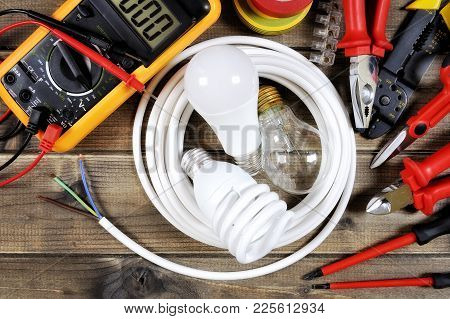 Light Bulbs Inside A White Roll Of Electric Cable And Work Tools On An Antique Wooden Desk.