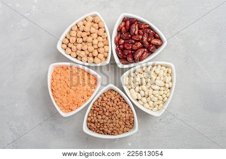 Selection Of Dry Legumes, Lentils And Peas In White Bowls On Gray Concrete Background. Top View, Fla