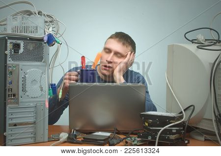Tired And Bored Computer Repairman Is Sitting On His Workplace And Is Sleeping. Computer Technician