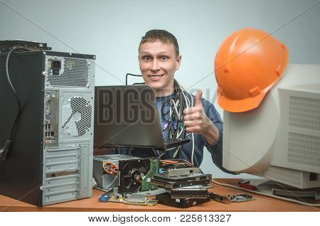 Happy Computer Technician Works On Laptop Computer And Showing Thumbs Up. Pc Repair Service Center.
