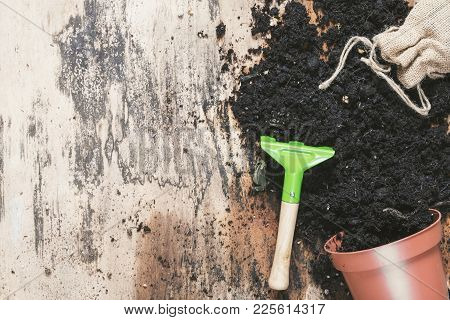 Small Rake And Flower Pot With Soil - Spring Gardening Theme Image With An Overturned Flower Pot Ful