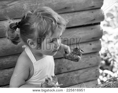 Cute Little Boy With Blond Hair Ponytail In White Pinafore Eats Fruit Cake With Berries On Summer Da