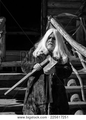 Old Man Druid With Long Silver Hair And Beard In Fur Coat Stands With Axe On Log House Background