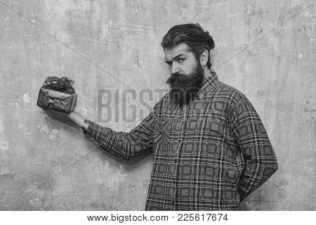 Frown Bearded Man, Caucasian Hipster, With Long Beard And Moustache In Plaid Shirt Holds Red Gift Bo