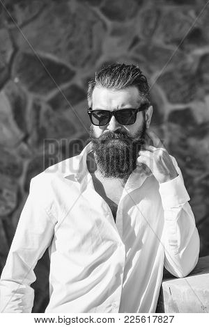 Handsome Young Stylish Hipster Man With Long Beard And Sun Glasses In White Shirt Standing Outdoor O