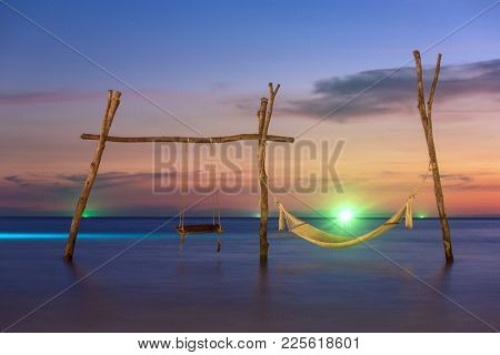Wooden swing and hammock on the beach of Koh Kood island in Thailand.