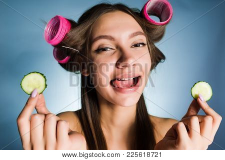 Happy Woman With Big Curlers On Her Head Holds A Cucumber