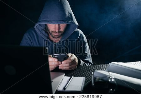 Male Hacker In A Sweatshirt With A Hood Sits At The Table And Looks Into The Phone