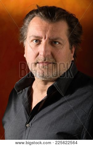 Portrait of fifty years old man with unbuttoned shirt. Serious attitude