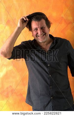 Portrait of a fifty year old man with unbuttoned shirt. He laughs while holding his hat