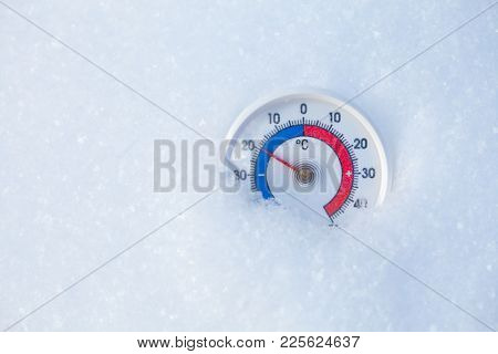 Thermometer with celsius scale placed in a fresh snow showing sub-zero temperature minus 20 degree - cold winter weather concept