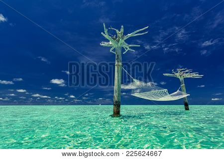 Empty hammock in the middle of tropical lagoon, Maldives Islands