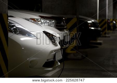 White Electric Car In Underground Parking. Fuel Gasoline Car On Background .connected Power Plug. Fu