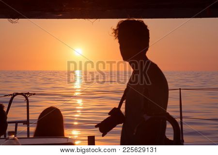 Palma, Mallorca, Spain On July 15, 2014: Young Man With Camera In Silhouette At Sunrise On A Boat On
