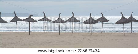 Parasol Lineup Panorama On Sandy Beach With White Sunny Ocean And Soft Blue Sky.