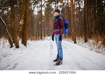 Side View Of Girl In Hat With Backpack Over Winter Forest In Afternoon