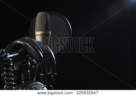 Microphone And Hedaphones On Tripod In Studio