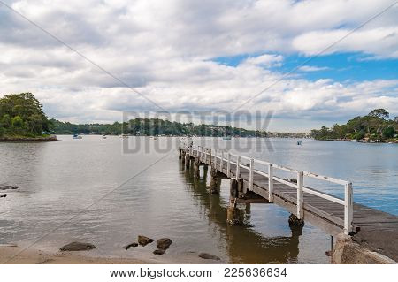Wooden Jetty With Distant View Of Houses Over Water. Sydney Suburbian Landscape. Como Suburb