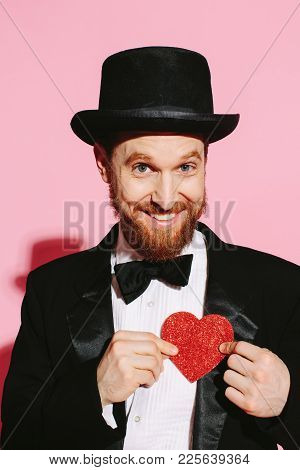 Ginger Bearded Man With Big Smile, Tux And Top Hat Holding A Red Heart