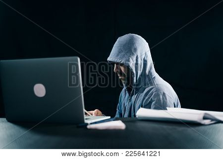 Male Hacker In A Sweatshirt With A Hood Sitting At The Table