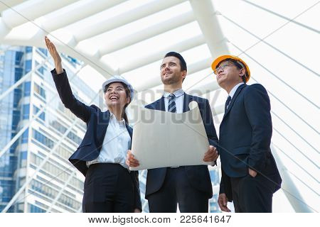 Engineering And Architecture Concept,engineers Working On A Building Site Holding A Blueprints,archi