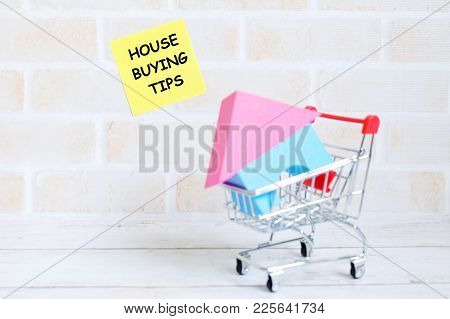 Selective Focus Of Yellow Sticky Notes Written With House Buying Tips With House Model And Trolley O