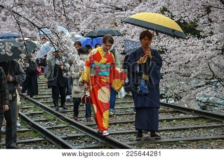 Kyoto, Japan - April  8, 2017 - Kimono-clad Couple And Others Walk Along The Railway Tracks Of The K