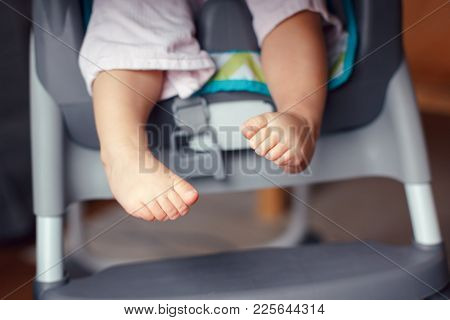 Closeup Of Adorable Chubby Baby Legs Feet. Small Kid Sitting In High Chair. Macro Detail Of Cute Chi