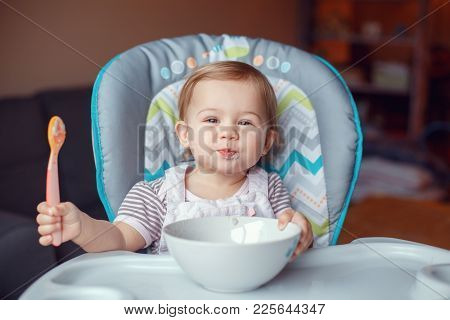 Portrait Of Cute Adorable Caucasian Child Kid Girl Sitting In High Chair Eating Cereal With Spoon. E