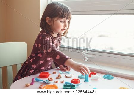 Portrait Of Cute White Caucasian Preschooler Girl Playing Plasticine Playdough Indoors At Home. Earl