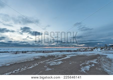Snow Fences Along The Beach With A Peach Colored Sunset On Lake Michigan