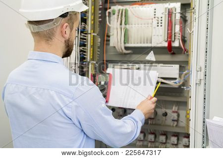 Engineer In White Helmet Reads Design Drawing Against Electric Industrial Panel. Service Worker Anal