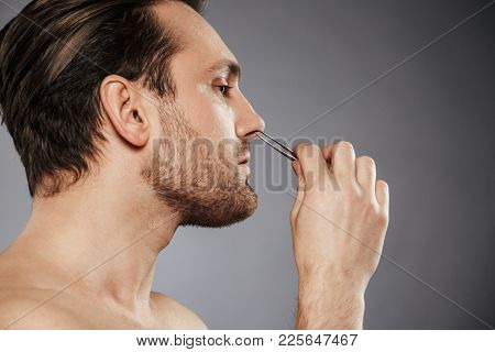 Side view portrait of a confident man removing nose hair with tweezers isolated over gray background