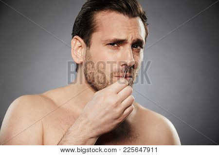 Portrait of a scared man removing nose hair with tweezers isolated over gray background