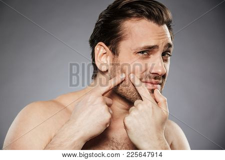 Close up portrait of a scared shirtless man squeezing pimple on his face isolated over gray background