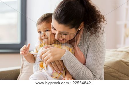 family, child and motherhood concept - happy smiling mother with little baby daughter at home