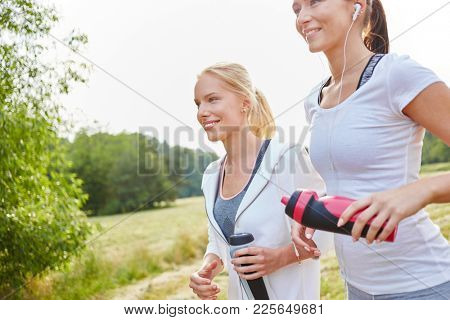 Two young women jogging in the park together in summer