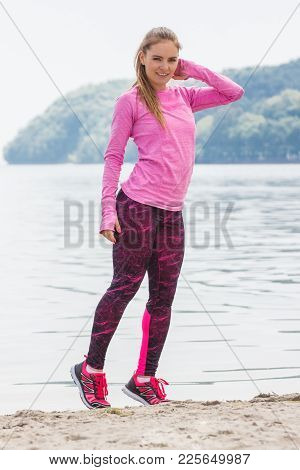 Slim Girl Wearing Sporty Clothes And Exercising Or Stretching On Beach At Sea, Healthy And Active Li