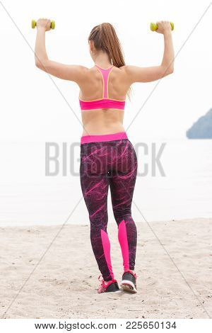 Slim Fit Girl With Tape Measure Wearing Sporty Clothes And Exercising With Dumbbells On Beach At Sea